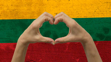 With a stylized Lithuanian flag background an anonymous persons hands being held in the form of a heart, symbolizing love and patriotism for Lithuania.