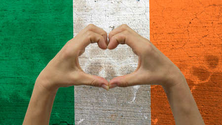 With a stylized Irish flag background an anonymous persons hands being held in the form of a heart, symbolizing love and patriotism for Ireland.