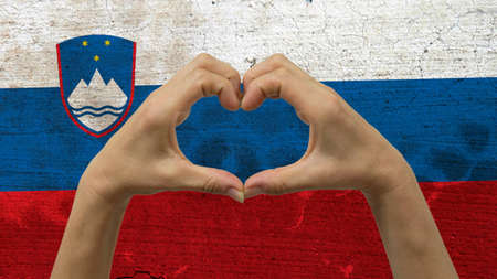 With a stylized Slovenia flag background an anonymous persons hands being held in the form of a heart, symbolizing love and patriotism for Slovenia.