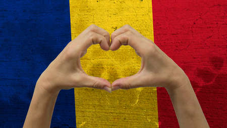 With a stylized Romania flag background an anonymous persons hands being held in the form of a heart, symbolizing love and patriotism for Romania.
