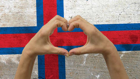 With a stylized Faroe Islands flag background an anonymous persons hands being held in the form of a heart, symbolizing love and patriotism for the Faroe Islands.