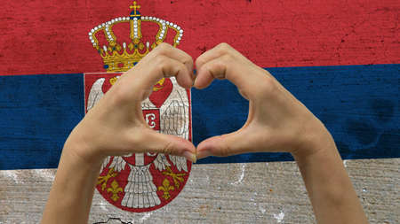 With a stylized Serbia flag background an anonymous persons hands being held in the form of a heart, symbolizing love and patriotism for Serbia. Stock Photo