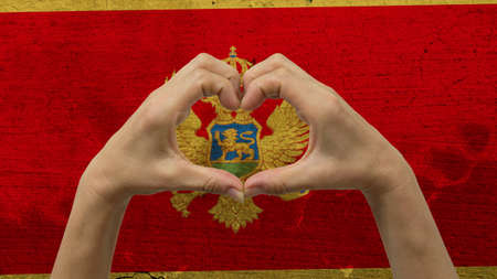With a stylized Montenegro flag background an anonymous persons hands being held in the form of a heart, symbolizing love and patriotism for Montenegro.