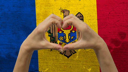 With a stylized Moldova flag background an anonymous persons hands being held in the form of a heart, symbolizing love and patriotism for Moldova.