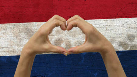 With a stylized Netherlands flag background an anonymous persons hands being held in the form of a heart, symbolizing love and patriotism for Netherlands. Stock Photo