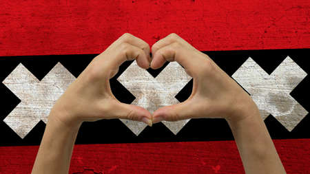 With a stylized Amsterdam flag background an anonymous persons hands being held in the form of a heart, symbolizing love and patriotism for Amsterdam. Stock Photo