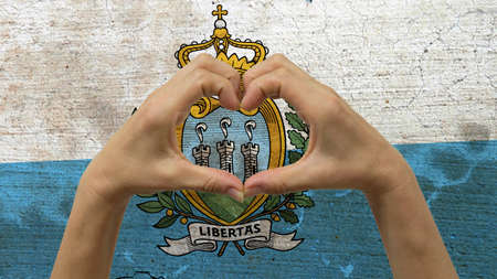 With a stylized San Marino flag background an anonymous persons hands being held in the form of a heart, symbolizing love and patriotism for San Marino. Stock Photo