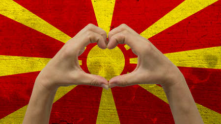 With a stylized Macedonia flag background an anonymous persons hands being held in the form of a heart, symbolizing love and patriotism for Macedonia.