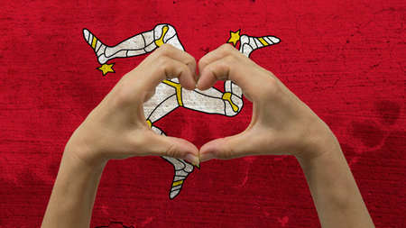 With a stylized Isle of Man flag background an anonymous persons hands being held in the form of a heart, symbolizing love and patriotism for the Isle of Man.
