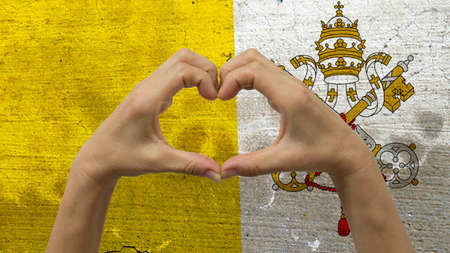 With a stylized Vatican City flag background an anonymous persons hands being held in the form of a heart, symbolizing love and patriotism for the Vatican City.