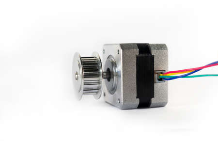 Electric stepper motor with a shiny metal timing pulley mounted to the shaft is laying down on its side ready to be used in a mechanical engineering or hobby robotics project. Stock Photo