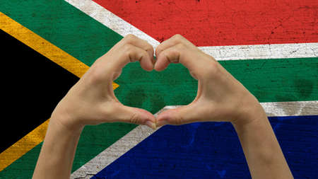 With a stylized South African flag background an anonymous persons hands being held in the form of a heart, symbolizing love and patriotism for South Africa. Stock Photo