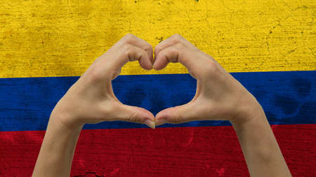 With a stylized Colombian flag background an anonymous persons hands being held in the form of a heart, symbolizing love and patriotism for Colombia.