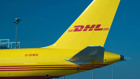 SCHKEUDITZ, GERMANY - SEPT 29, 2017: Close up shot if the tail of a cargo plane with the DHL logo in it at the DHL package sorting facility near Leipzig Germany.