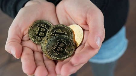 A close up shot of a woman holding her Bitcoin cryptocurrency filled hands open.