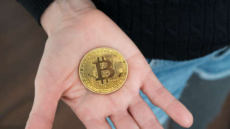 Close up shot of a woman with a Bitcoin cryptocurrency coin in her open hand. Zdjęcie Seryjne