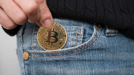 Close up shot of a woman putting a Bitcoin cryptocurrency coin into her front jeans pocket.