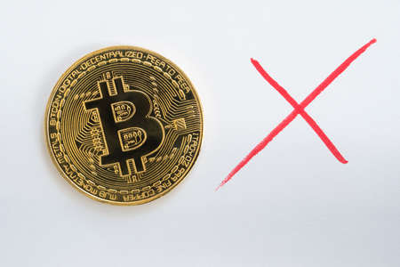 Bitcoin BTC cryptocurrency coin on a white background with a hand drawn red x mark.