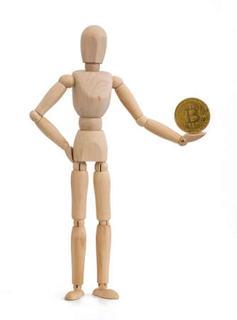 A wooden mannequin holding a Bitcoin BTC cryptocurrency coin in one hand against a white background.