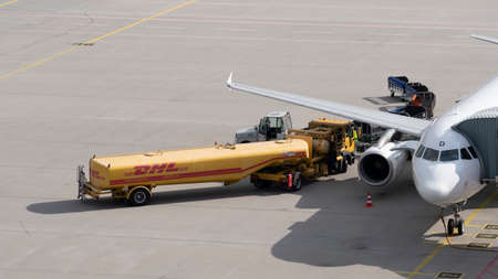SCHKEUDITZ, GERMANY - AUG 15, 2018: A DHL fuel tanker delivery truck loads jet fuel onto a passenger jet airplane at the Halle - Leipzig airport in Germany Redakční