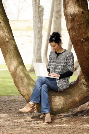 30-35 years old beautiful woman portrait working on laptop computer natural in park photo
