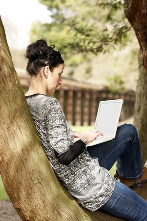 30-35 years old beautiful woman portrait working on laptop computer dinking natural in park photo