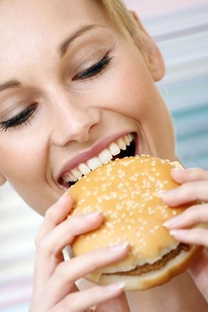 adult sandwich: 25-30 close-up portrait of young woman with hamburger focus on face