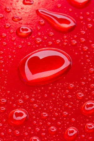 heart reflected in drops on red background photo