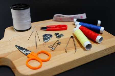 top view equipment for sewing about fashion designer on wooden , black background.