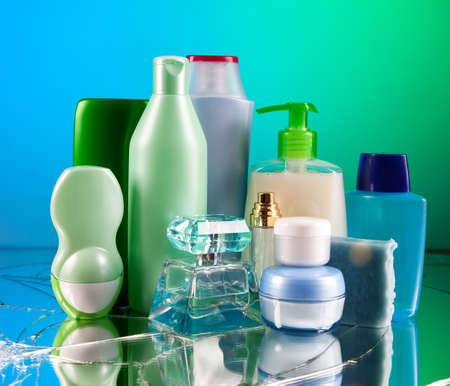 perfumery concept: Group of empty cosmetic bottles on beautiful green and blue mirror Stock Photo