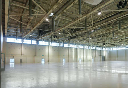 Large empty space in hangar with lights through the windows Stock Photo