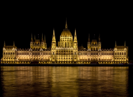 Parliament in Budapest lit at night, glowing in the Danube River
