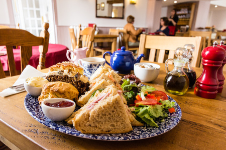 A hearty lunch with sandwiches, scones, cakes, and tea