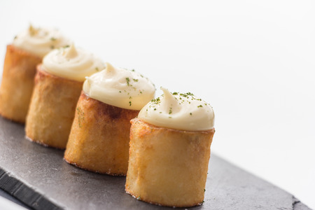 A zesty variation on patatas bravas, with partially hollowed potato rolls filled with a spicy tomato sauce topped with a creamy garlic sauce and a springled with a mix of herbs and spices