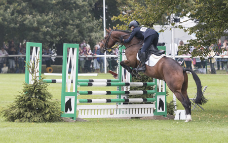 guides: Burghley, StamfordUK - September 5, 2014: Italian riderVittoria Panizzon guides Super Cillious over the first fence in the Dubarry Burghley Young Event - Five Year Old Final.