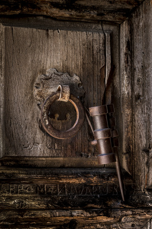 A door knocker, etched in Arabic, with Roman letters carbed below in the wood.  The