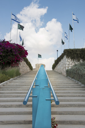 Israeli military flags flank stairs and a blue rail leading to the Latrun fortress