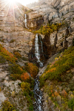 The sun rises over cliffs above a waterfall with autumn leaves changing colors