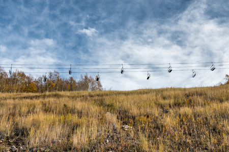A ski chair lift sits empty over an alpine meadow during autumn with wispy clouds overhead.