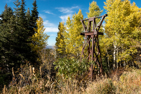 A rusty, derelict ski chair lift tower overgrown with trees and bush, sits in an aspen grove with autumn leaves