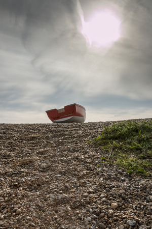 Abandoned boat sitting atop a dune at a pebble-covered beach