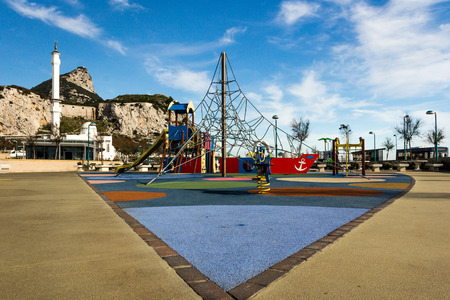 A playground with jungle gym, rope ladder, swing, and slide at a park Standard-Bild