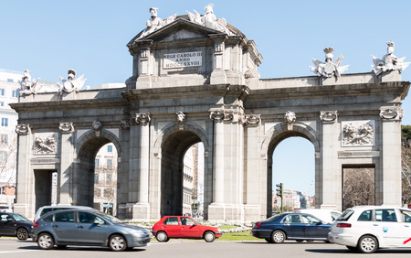 Cars pass by the Alcala Arch at the Plaza de la Independencia in Madrid