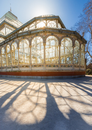 A warm, spring sun adds a rich glow to the glass as it sets behind the Crystal Palace, in Buen Park, Madrid, Spain.