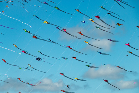 Colorful triangular kites fill the blue sky