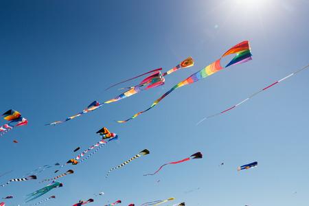 papalote: Grandes cometas de colores vuelan alto contra un cielo azul con los rayos del sol y la flama del sol brillando Foto de archivo