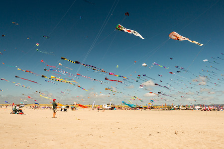 Families and individuals hoist colorful kites on the beach at the annual kite festival in Long Beach, Washington