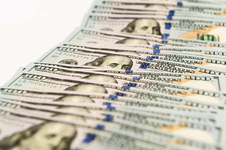 banknotes: Many hundred dollar cash banknotes spread on white surface