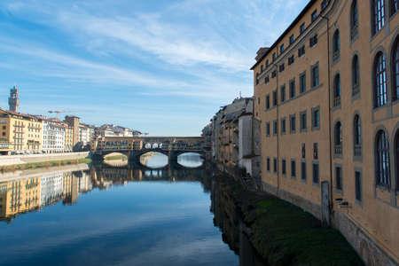 ponte vecchio: View of Arno river embankment with architecture and Ponte Vecchio bridge reflected on water