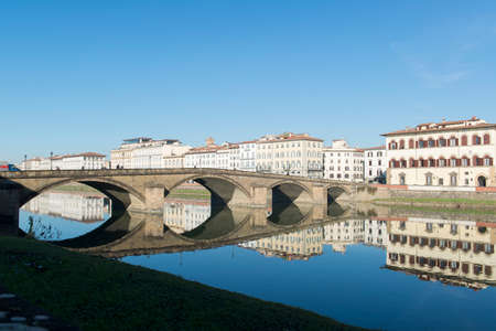 View of Arno river embankment with architecture and buildings and bridge reflected on water